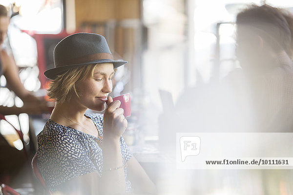 Woman in hat drinking coffee in cafe