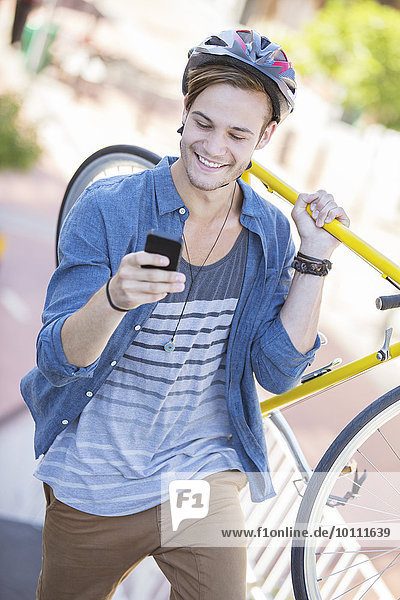 Young man with helmet carrying bicycle and texting on cell phone