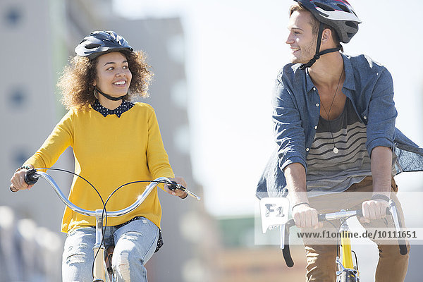 Young couple with helmets riding bicycles in city