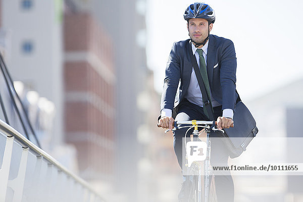 Businessman in suit and helmet riding bicycle in city