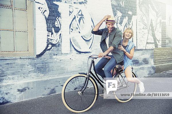 Portrait Verspieltes Paar beim Fahrradfahren entlang der städtischen Graffiti-Wand