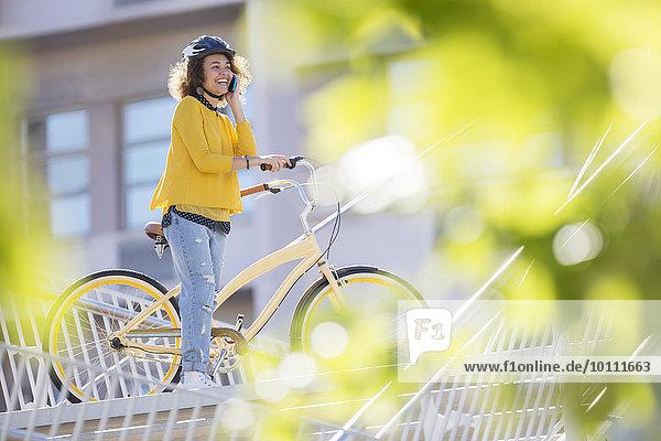 Lächelnde Frau beim Telefonieren auf dem Fahrrad in der Stadt
