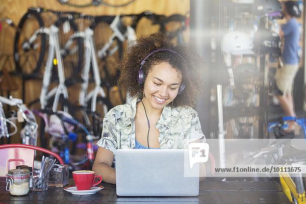 Lächelnde Frau mit Kopfhörer bei der Arbeit am Laptop im Fahrradgeschäft