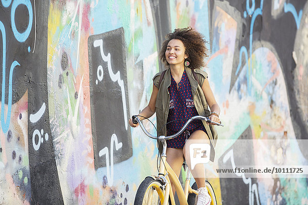 Smiling brunette woman riding bicycle along urban multicolor graffiti wall