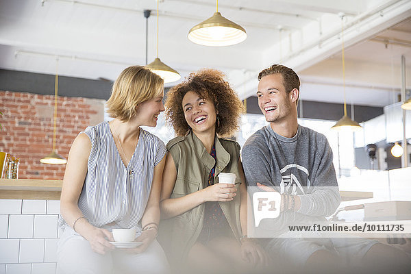 Lachende Freunde beim Kaffeetrinken im Cafe