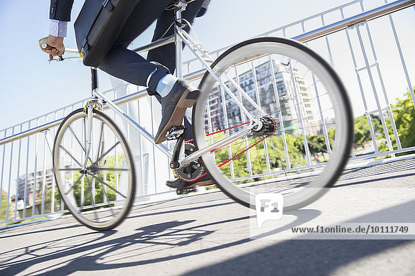 Low section businessman in suit riding bicycle on sunny urban sidewalk