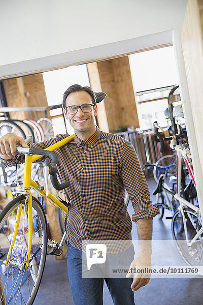 Portrait smiling man with eyeglasses carrying bicycle in bicycle shop