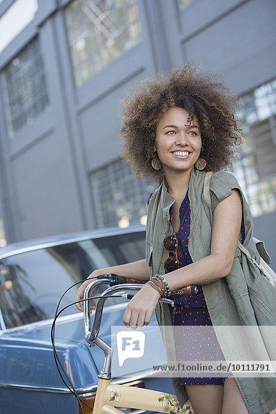 Lächelnde junge Frau mit Afro-Haltefahrrad auf urbaner Straße
