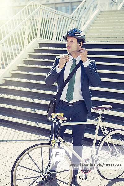 Businessman in suit with bicycle fastening helmet near urban stairs