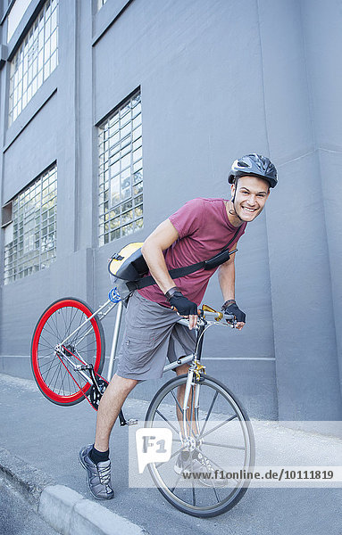 Portrait smiling bicycle messenger with helmet leaning forward on urban sidewalk