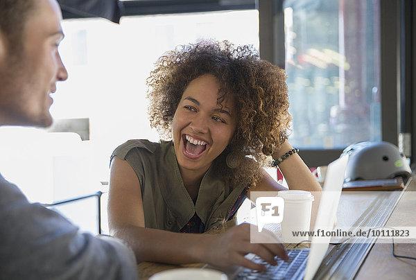 Enthusiastische Frau lacht über Laptop im Cafe