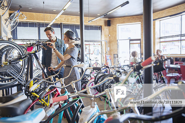 Couple browsing bicycles on rack in bicycle shop