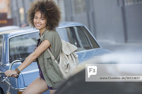 Portrait lächelnde Frau mit Afro auf dem Fahrrad in der Stadtstraße