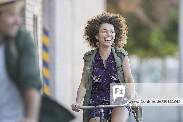 Enthusiastic woman with afro riding bicycle
