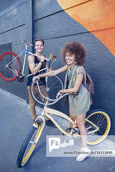 Portrait lächelnde Freunde mit Fahrrädern an der Stadtmauer