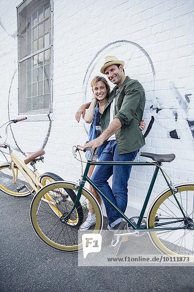 Porträt eines lächelnden Paares mit Fahrrädern an der Stadtmauer