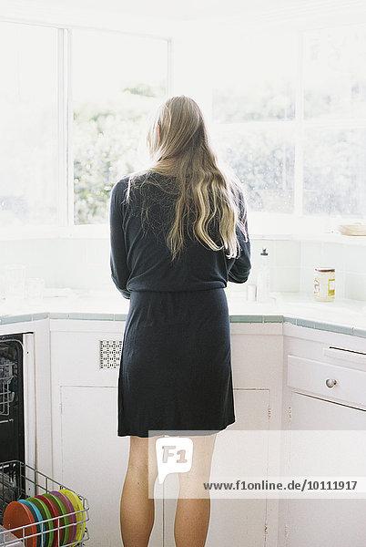 Spülbecken stehend blond Frau Küche lang langes langer lange Rückansicht Ansicht Haar