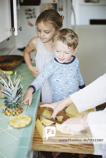Woman cutting a fresh pineapple for her children.