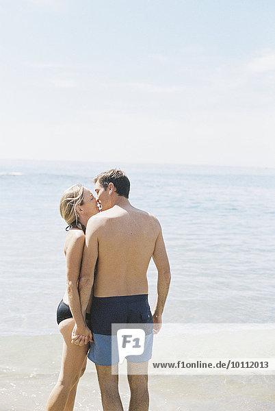 stehend Strand küssen Badebekleidung Ozean Sand