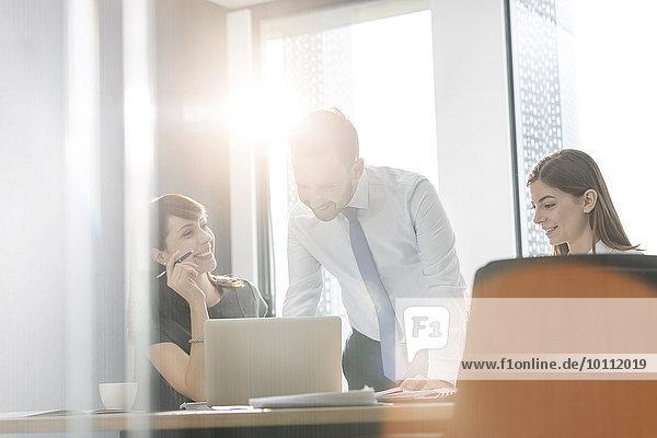 Geschäftsleute arbeiten am Laptop im sonnigen Konferenzraum Meeting