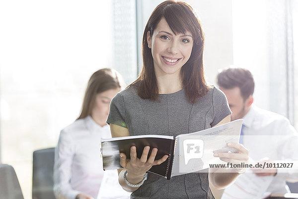 Portrait lächelnde Geschäftsfrau Holding-Bericht