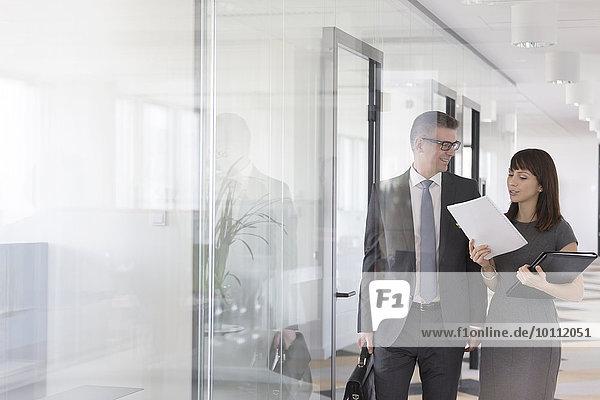 Geschäftsmann und Geschäftsfrau besprechen Bericht im Büroflur