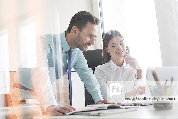 Geschäftsmann und Geschäftsfrau bei der Arbeit am Laptop im Büro