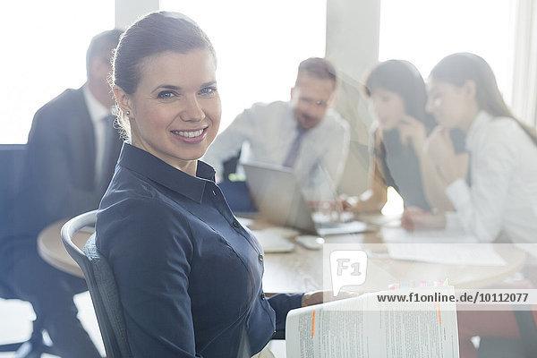 Portrait selbstbewusste brünette Geschäftsfrau mit Bericht in Konferenzraumbesprechung