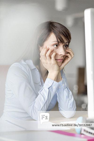 Frustrierte brünette Geschäftsfrau arbeitet am Computer im Büro
