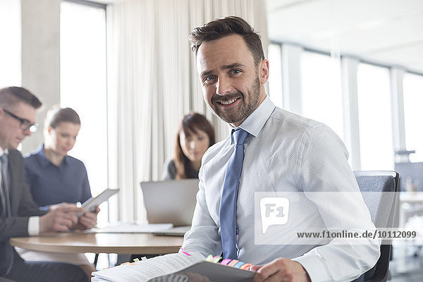 Porträt lächelnder brünetter Geschäftsmann mit Bericht im Konferenzsaal