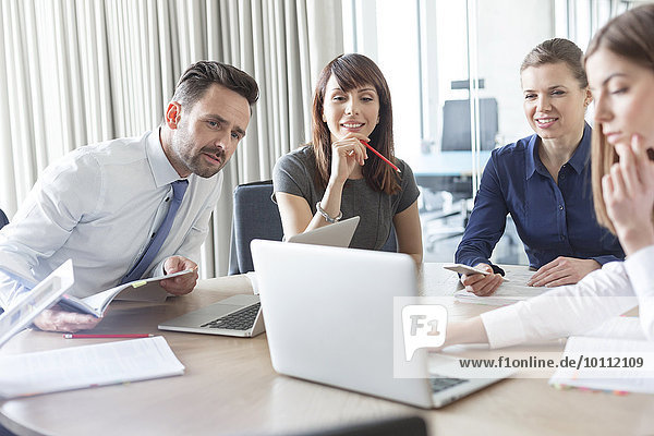 Geschäftsleute arbeiten am Laptop im Konferenzraum