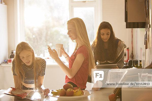 benutzen Jugendlicher Kurznachricht Küche Zeitschrift Tablet PC Mädchen vorlesen