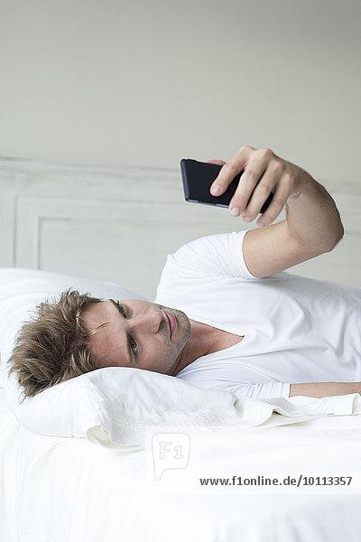 Mann mit Smartphone im Bett