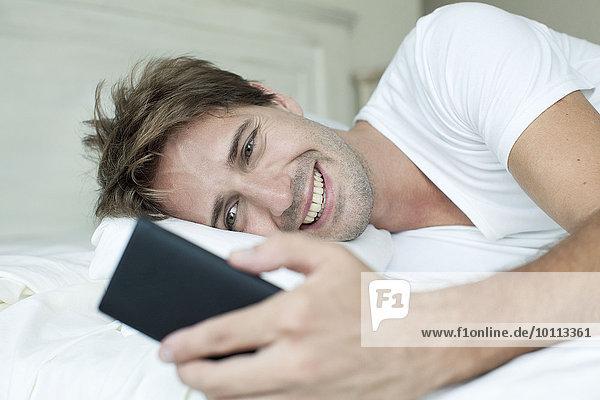 Mann im Bett mit Smartphone