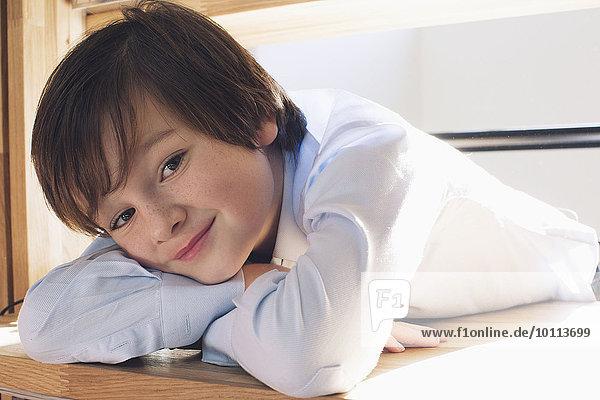 Junge ruht Kopf auf Armen  lächelnd  Portrait