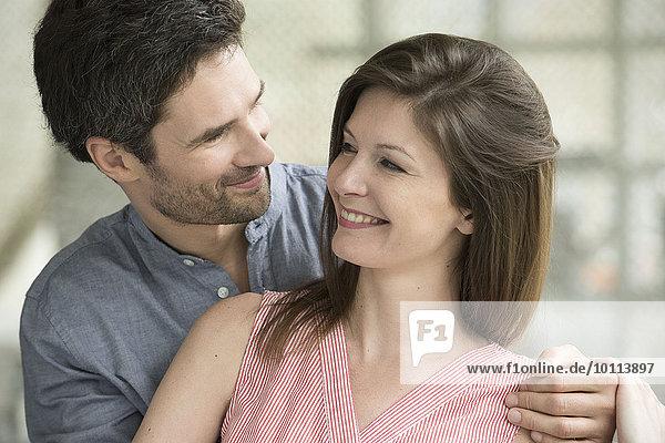 Ein Paar lächelt sich an.