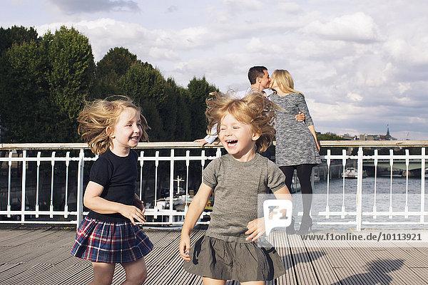 Kleine Mädchen spielen im Freien  während ihre Eltern sich im Hintergrund küssen.