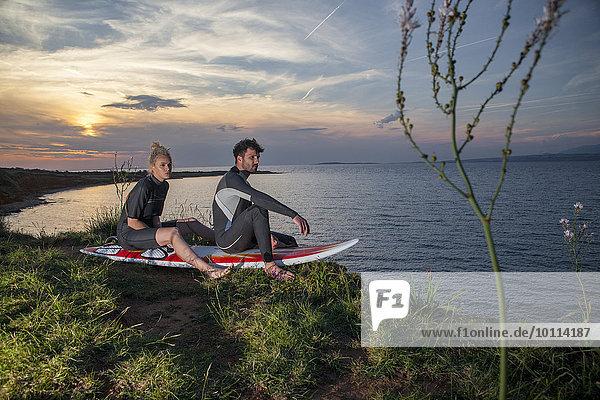 Surfers sitting on surfboard
