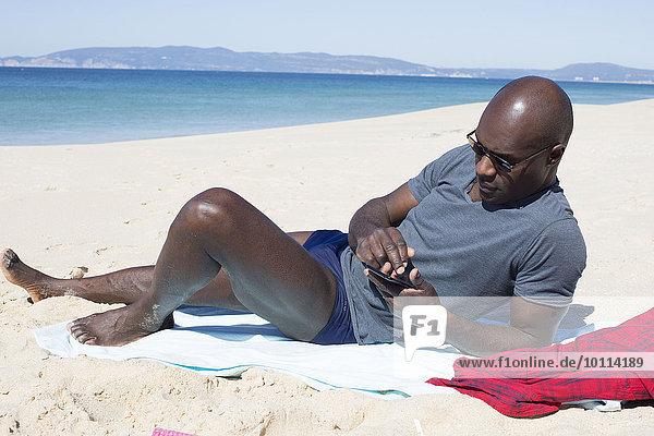 liegend liegen liegt liegendes liegender liegende daliegen Mann Strand benutzt Smartphone