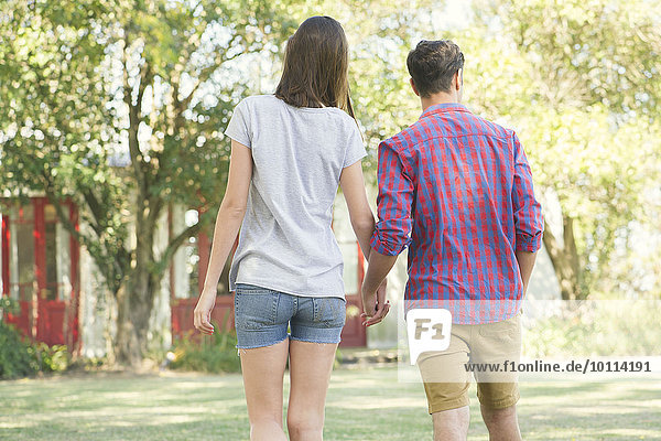 Couple walking and holding hands outdoors  rear view