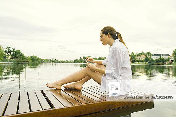Woman relaxing on lake dock using digital tablet