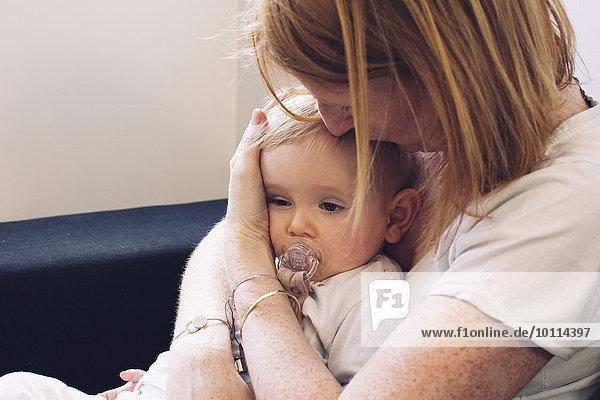 Mutter hält Kleinkind auf Schoß