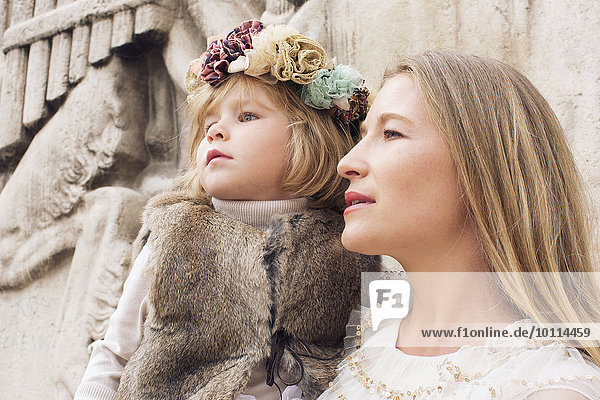 Mother and young daughter together outdoors  looking away attentively
