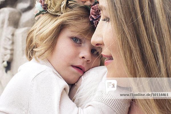Kleines Mädchen  das seinen Kopf auf die Schulter seiner Mutter legt.