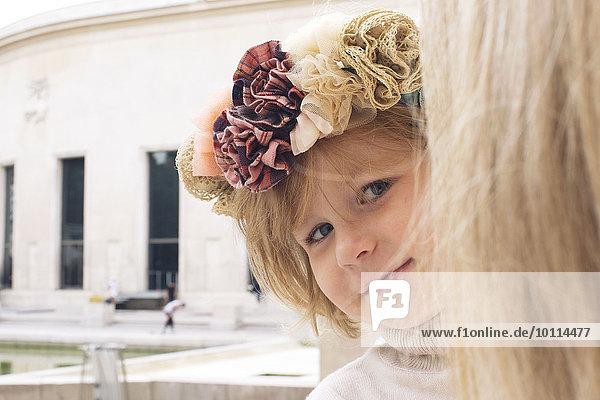 Kleines Mädchen  das um den Kopf der Mutter schaut  Porträt