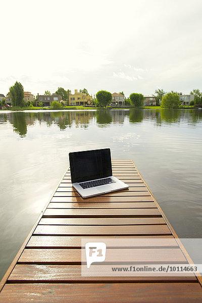 Laptop computer on lake pier