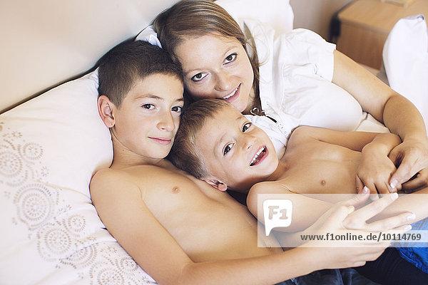 Mutter und kleine Söhne entspannen gemeinsam auf dem Bett  Porträt