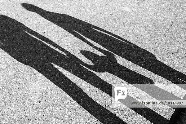 Schatten der Eltern und des Kindes  das sich an den Händen hält
