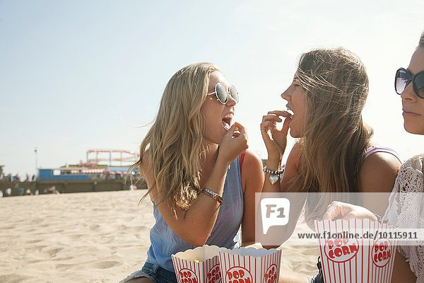 Drei junge Frauen  die am Strand sitzen und Popcorn essen