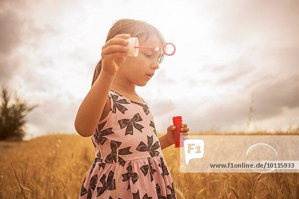 Mädchen bläst Blasen im Weizenfeld